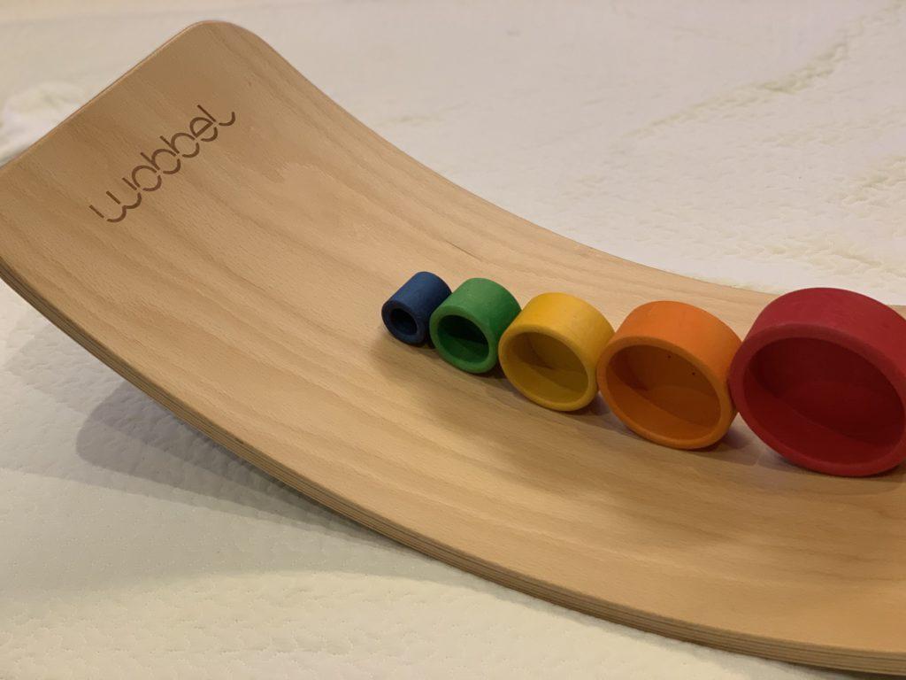 ウォーベルにグリムスのコップ重ねを順番にコロコロ。1歳でも転がす遊びで楽しめます。