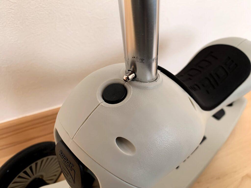 スクートアンドライドの組み立てを紹介している画像。ハンドルのロックピンをシート部に押し込もうとしている所